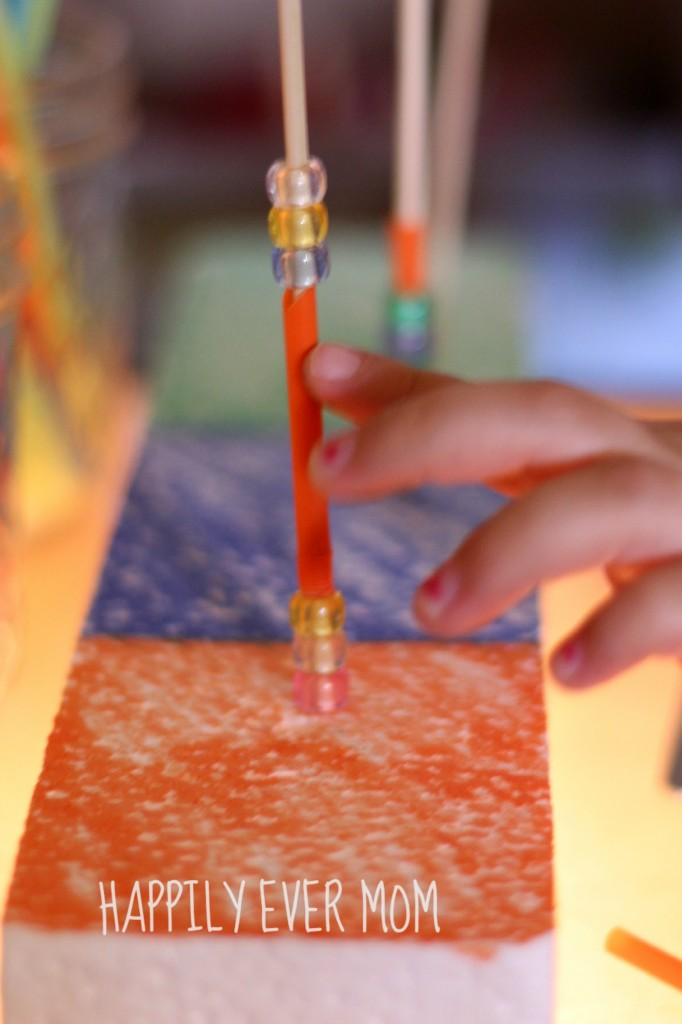 Fine Motor Station on the light table counting beads on a skewer from Happilyevermom