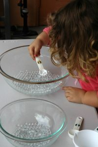 Introducing water beads by scooping into bowls from Happilyevermom